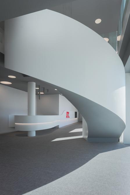 Escalera blanca en espiral en hall de oficinas modernas con mostrador en blanco y curva con iluminacion led
