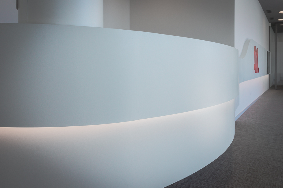 Mostrador blanco y en curva moderno en hall de oficinas.
