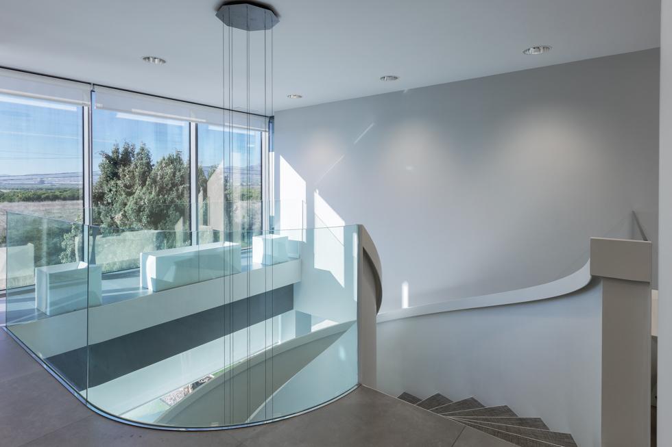 Escalera blanca y minimalista en espiral en hall de oficinas modernas con lampara moderna colgante