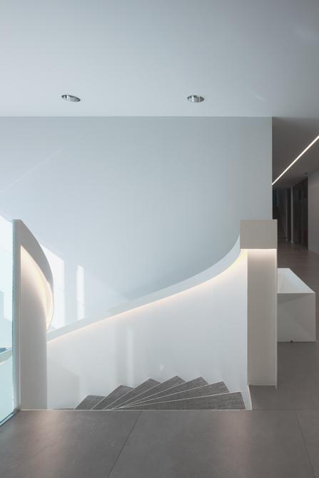 Escalera blanca y gris en espiral en hall de oficinas modernas.