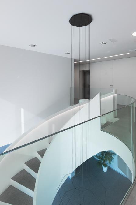 Escalera blanca en espiral en hall de oficinas modernas con barandilla de cristal