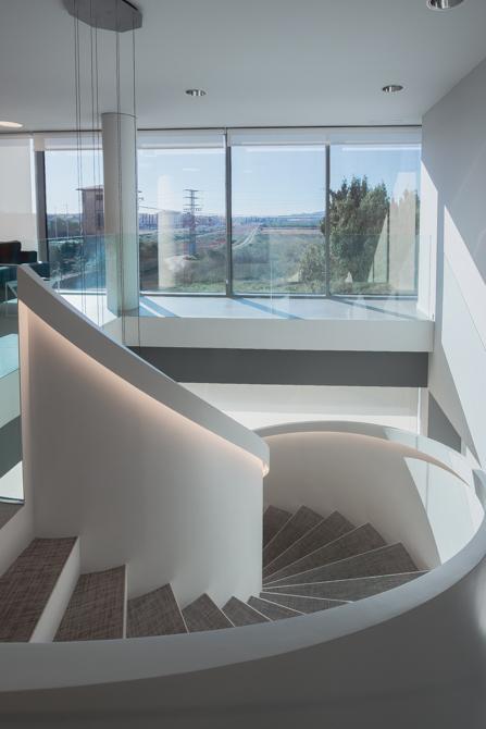 Escalera blanca en espiral en hall de oficinas modernas.