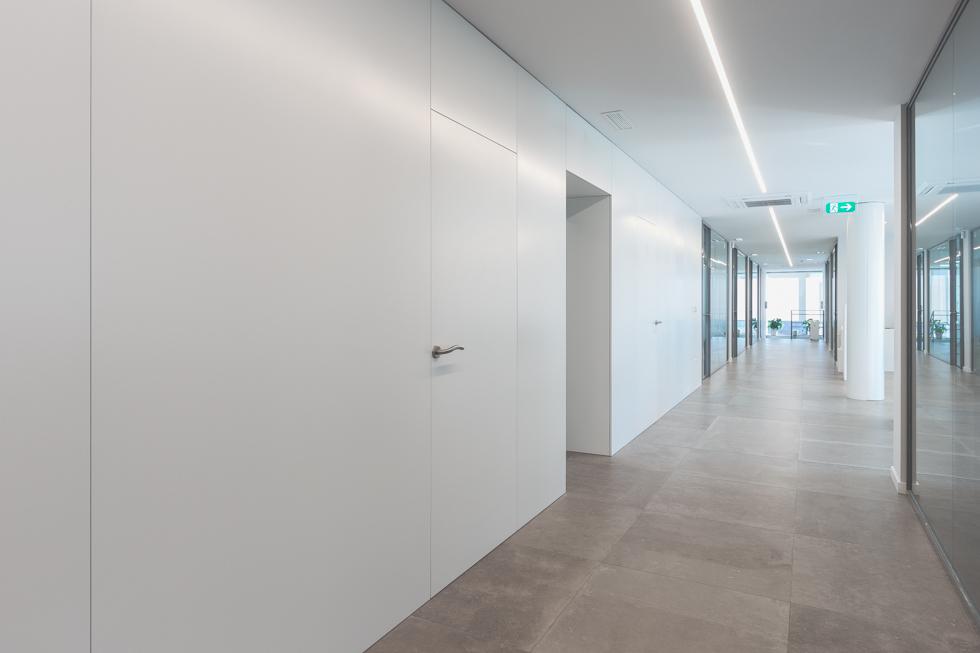 Pasillo de oficinas modernas con puertas blancas, puertas de cristal y suelo gris