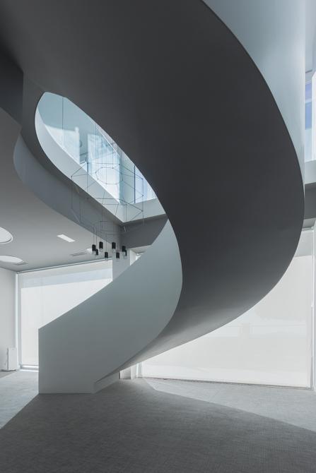 Escalera en espiral blanca y minimalista en oficinas modernas