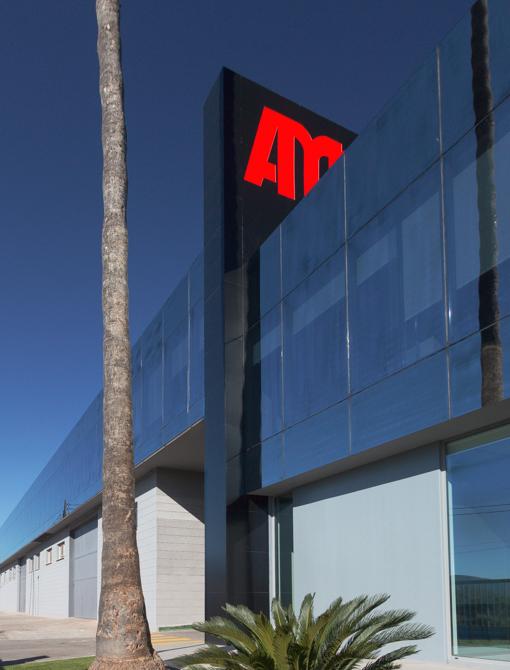 Edificio de oficinas con fachada de cristal oscuro y jardin con palmera