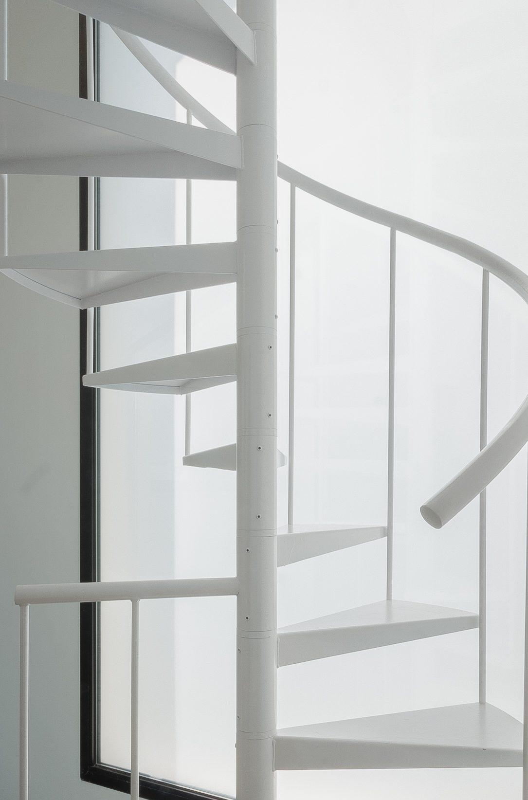 EScalera de metal blanca de caracol con gran vemntanal que la ilumina al lado