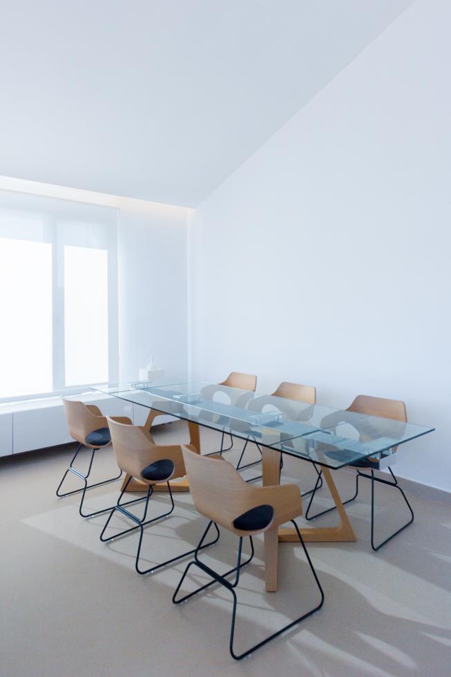 Fotografia de mesa de comedor de cristal con sillas de madera para 6 personas en casa de techos inclinados y altos