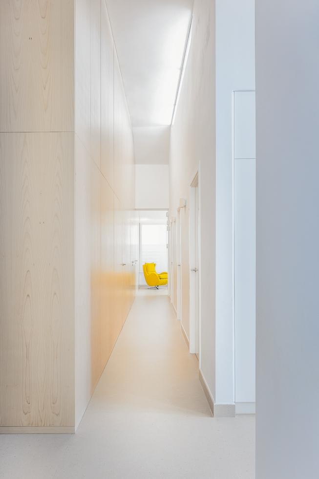 Pasillo con lucernario en techos altos. Sillon amarillo. Armario de madera de haya con puertas invisibles.