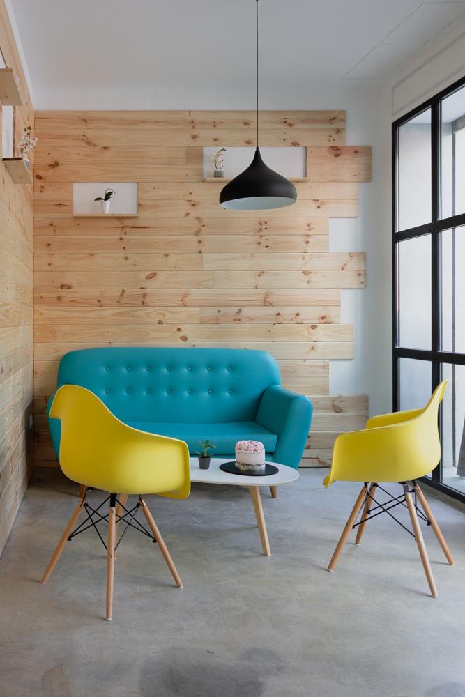 cafetería-de-diseño-en-Valencia moderna y colorida con parede de madera y suelo de hormigon con sofas de colores