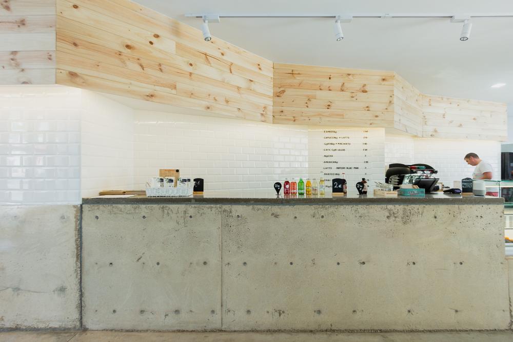 cafetería-de-diseño-en-Valencia. con mostrador de hormigon y pared de ladrillos metro y madera