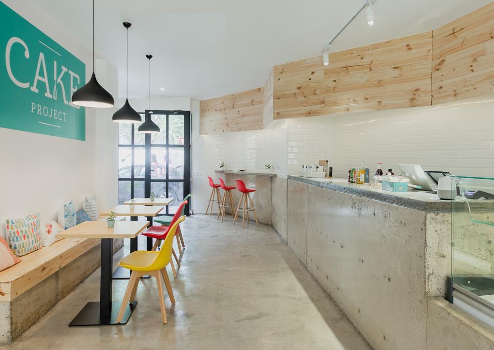cafetería-de-diseño-en-Valencia-con mostrador de hormigon moderno y minimalista.ladrillos tipo metro y madera. sillas de colores