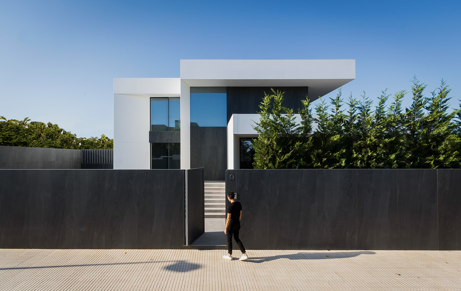 Entarada de casa moderna y minamalista blanca con valla negra